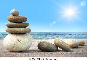Stack of spa rocks on wood against blue sky