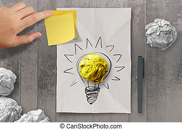 sticky note with another idea light bulb on crumpled paper as creative concept
