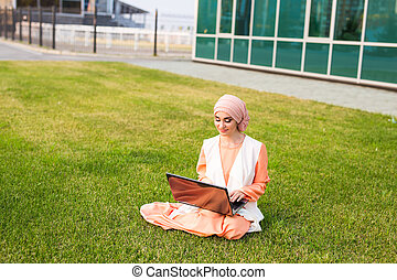 Successful Muslim woman and laptop. Arab businesswoman wearing hijab working on a laptop in the park.