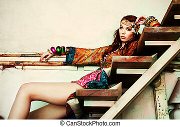 young woman in colorfull summer clothes sit on stairs indoor shot