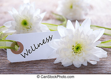 Tag with Wellness on Wooden Background with White Flowers