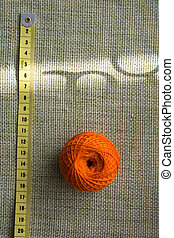 Tangle of orange thread and a measuring tape on a green cloth