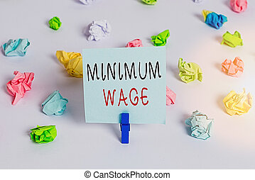 Text sign showing Minimum Wage. Conceptual photo the lowest wage permitted by law or by a special agreement Colored crumpled papers empty reminder white floor background clothespin.