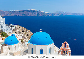 The most famous church on Santorini Island, Crete, Greece. Bell tower and cupolas of classical orthodox Greek church with view of Mediterranean sea and Spinalonga island