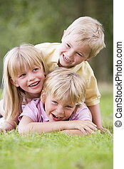 Three young children playing outdoors smiling