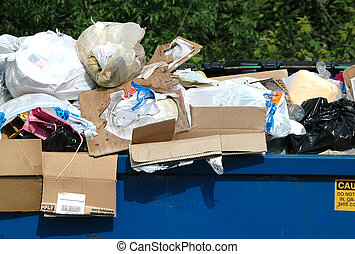 Trash and garbage stacked outside in a garbage container.