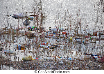 Trash floating polluting water in a pond.