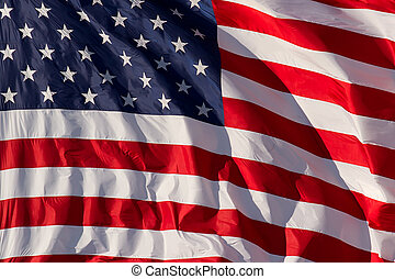 A detailed, vibrant USA flag flapping in the breeze and filling the shot.