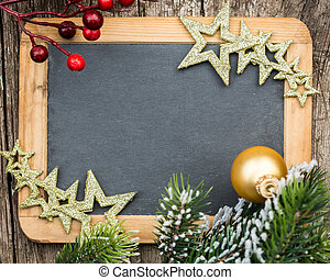 Vintage wooden blackboard blank framed in Christmas tree branch and decorations. Winter holidays concept. Copy space for your text