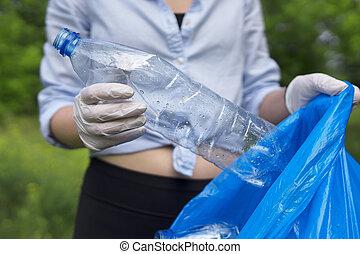 Volunteer holding plastic bottle. Environment pollution concept.