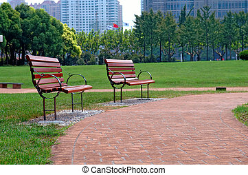 The walk way and bench of city park with building as background