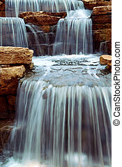 Beautiful cascading waterfall over natural rocks, landscaping element