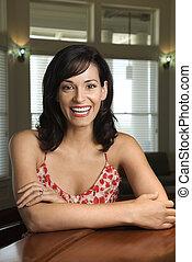 Woman at bar smiling.