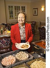 Woman at food buffet.