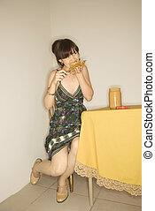 Woman eating at table.