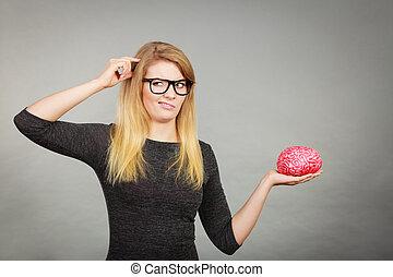 Woman in eyeglasses being confused holding brain