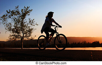 Woman riding her bike along the river at sunset
