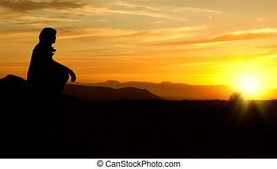 single adult woman silhouette on rock watching yellow and orange setting sun in distance