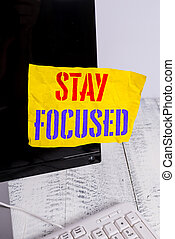 Writing note showing Stay Focused. Business photo showcasing Be attentive Concentrate Prioritize the task Avoid distractions Notation paper computer monitor screen near white keyboard.