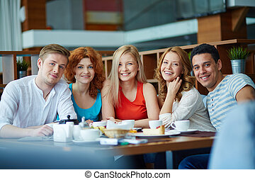 Young cheerful people sitting at café