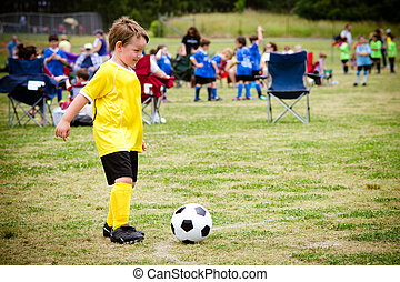 Young child boy playing soccer during organized league game