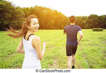 young couple running on the grass at morning