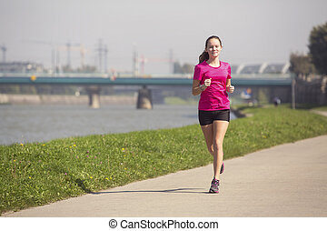 Young girl runs on Jogging track along the river in a big city. A healthy way of life.