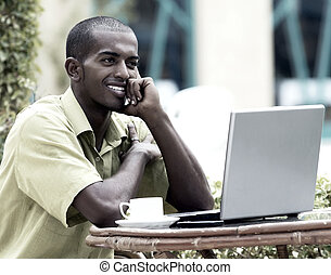Young happy man or student with laptop sitting at the table