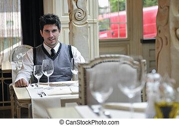 Young man sitting and waiting food at stylish restaurant