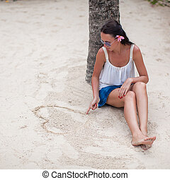 Young woman draws a heart in the sand with her finger