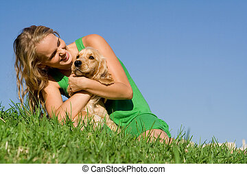 young woman or teen girl playing with pet cocker dog